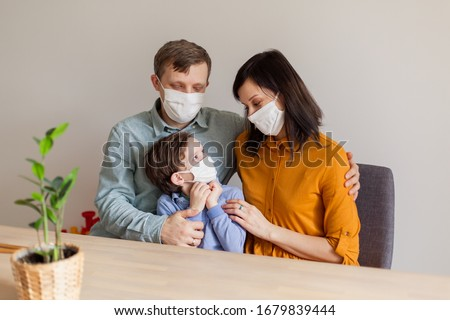 Young modern quarantined coronavirus family in medical masks. The call to stay home stop the pandemic. Self-isolation together is the solution. Care covid-19. mom dad son millennials #1679839444