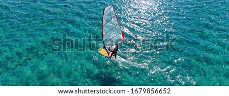 Aerial drone ultra wide photo of wind surfer cruising in high speed in tropical exotic bay
