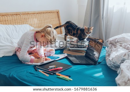 Caucasian girl child sitting in bed and learning online on laptop Internet. Virtual class lesson on video during self isolation at home. Distant remote video education. Modern school study for kids. #1679881636