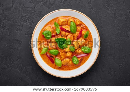 Thai Panang Chicken Curry in white plate at black slate background. Phanaeng Curry is thai cuisine dish with chicken, kaffir lime leaves, red curry sauce and vegetables. Thai food. Thai Red Curry #1679883595