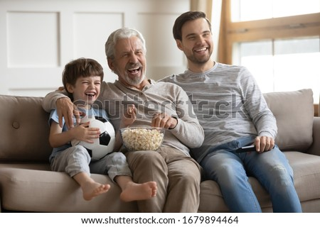 Overjoyed three generations of men relax on couch in living room watch football match eating popcorn together, happy little boy with dad and senior grandfather rest at home enjoy TV game on weekend