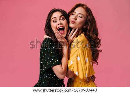 Surprised brunette woman looks into camera while her friend blowing kiss. Two beautiful and young girls posing on isolated backdrop #1679909440