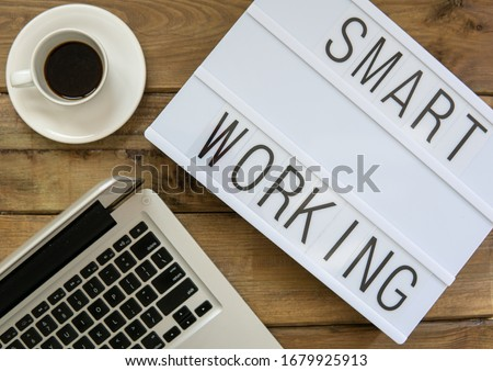 """Text """"smart working""""  written on white slate with personal computer and coffee on wooden background. Suitable for advertising Royalty-Free Stock Photo #1679925913"""