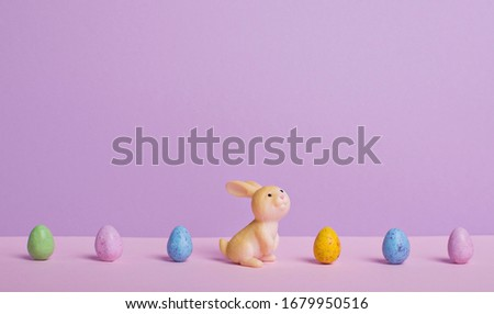 Cartoon easter bunny standing in a row of painted colored easter eggs, easter banner, place for text