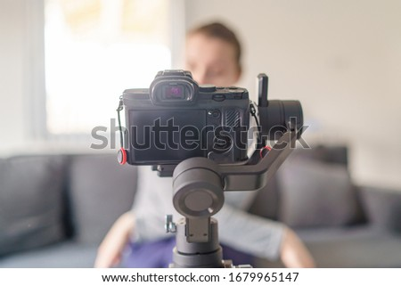 Gimbal with mirrorless camera blogger making video at home selective focus in day video blog Royalty-Free Stock Photo #1679965147