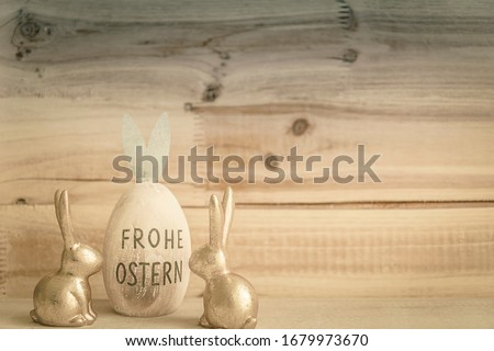 Two Easter Bunnies couple in front of wooden background with easter egg and text in german FROHE OSTERN means in english HAPPY EASTER #1679973670