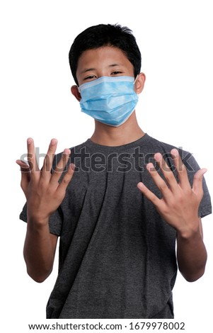 A young teenager boy wearing a face mask showing his back palms/hands isolated on white background #1679978002