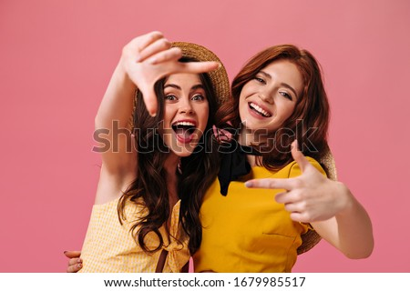 Curly women in yellow dresses take selfie on pink background. Young modern girls in fashionable clothes and straw hats are smiling #1679985517
