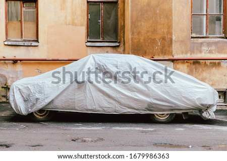 A machine with protective cloth thrown over is parked in the yard. Close up. Royalty-Free Stock Photo #1679986363