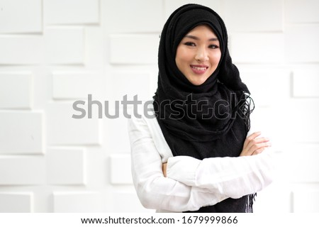 Portrait of happy beautiful asian arabic muslim woman with hijab dress relaxing.Young muslim girl smiling and look at camera on white wall background