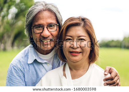 Portrait of happy senior adult elderly asian man and women couple smiling and looking at camera in the park.Retirement concept