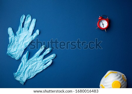 Protective respiratory face mask with surgical gloves and red alarm clock on blue background flat lay. Protection against the flu, coronavirus or transmissible infectious diseases. Top view. Royalty-Free Stock Photo #1680016483