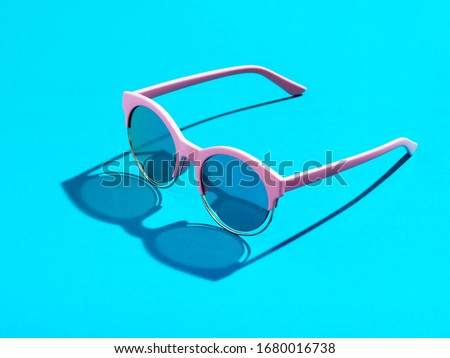 Trendy minimal style photography of  pink sunglasses on pastel blue background. Minimalist summer fashion or vacation concept. Sunny and vivid background with hard light and shadow.