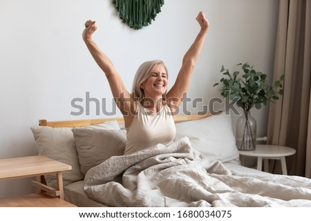 Joyful healthy older woman sitting on bed, waking up after good night rest on comfortable orthopedic mattress, rising up arms and stretching back. Happy mature grandma feeling energetic in morning. #1680034075