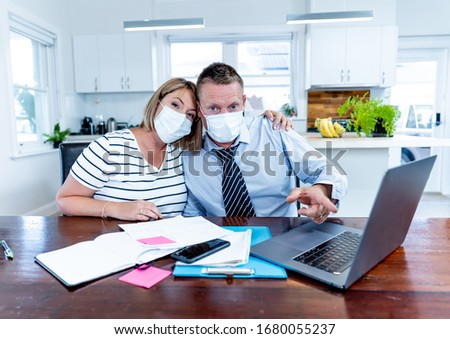 Coronavirus economic recession. Stressed couple with masks in self-isolation over home finances and small business debts during quarantine shutdown. impact of COVID-19 pandemic Global Economy Crisis. #1680055237