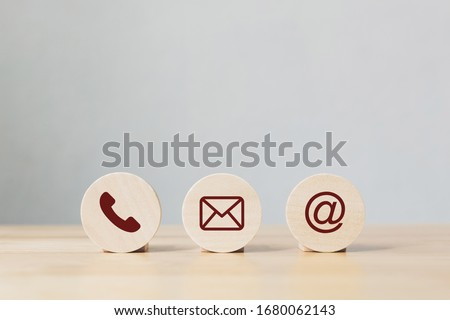 Wooden coins with symbol telephone, email, address. Website page contact us or e-mail marketing concept Royalty-Free Stock Photo #1680062143