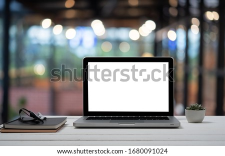 Laptop with blank screen and smartphone on table.