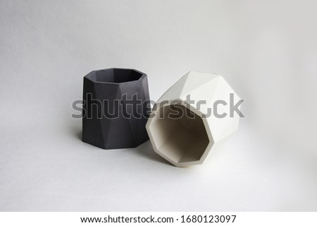 Concrete cement grey pot. Hand made concrete planters for succulents and cacti. Empty cup isolated on white background. Polygonal geometric shape for home decor.