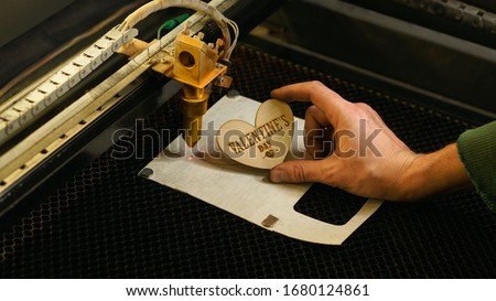 Laser cutting beam high precision on a plywood sheet. Modern technology of wood cutting. laser cut wooden 3d symbol of valentine's day.  Industrial laser engraving. CNC laser. Masterclass, workshop  #1680124861