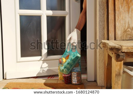 home delivering some groceries at quarantine time because of coronavirus infection COVID-19. man's hand is taking a shopping bag at he front door. Food delivery in net bag at door for self isolation Royalty-Free Stock Photo #1680124870