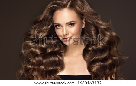 Beautiful model girl with long wavy and shiny hair . Brunette woman with curly hairstyle Royalty-Free Stock Photo #1680163132