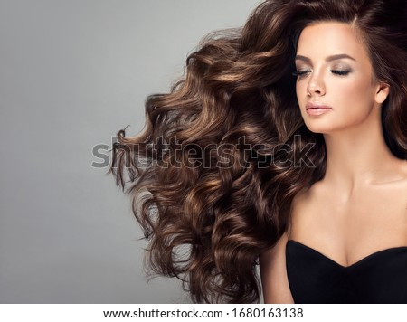 Beautiful model girl with long wavy and shiny hair . Brunette woman with curly hairstyle Royalty-Free Stock Photo #1680163138