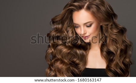 Beautiful model girl with long wavy and shiny hair . Brunette woman with curly hairstyle #1680163147