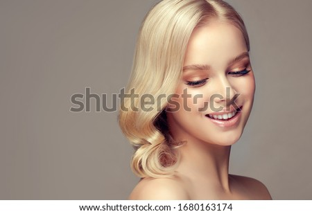 Blonde woman with curly beautiful hair  on gray background. Girl with  pleasant smile. Short wavy  hairstyle.  Clean and delicate look. Skin Care, beauty and  spa