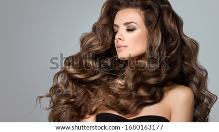 Beautiful model girl with long wavy and shiny hair . Brunette woman with curly hairstyle #1680163177