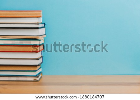 A simple composition of many hardback books, raw books on a wooden table and a bright blue background. back to school. Education. #1680164707