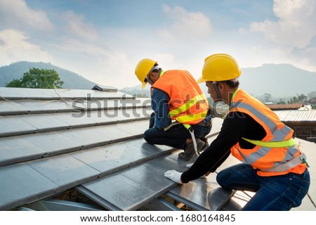 Engineers worker install new CPAC roof,Roofing tools,Electric drill used on new roofs with CPAC roof,Construction concepts. Royalty-Free Stock Photo #1680164845