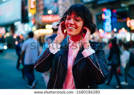 Cheerful woman teenager walking around evening megalopolis and relaxing with positive music, youthful hipster girl in electronic headphones listening audio playlist during leisure in New York #1680186280