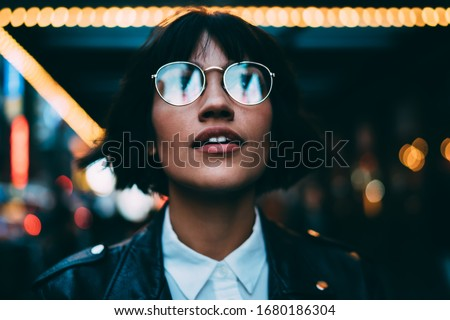 Youthful female traveller in stylish spectacles for vision correction spending time for walking around metropolitan downtown and explore New York nightlife on leisure, young woman in streetwear #1680186304