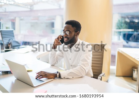 Dark skinned man in optical eyeglasses working on startup project research business information on laptop website, black male receiving cellphone call conversation via application for talking #1680193954