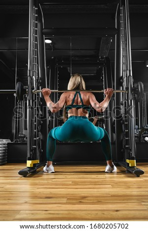 A girl is training her legs in the gym with a barbell. Sport lifestyle, keep fit, fitness motivation. dark background, copy space #1680205702