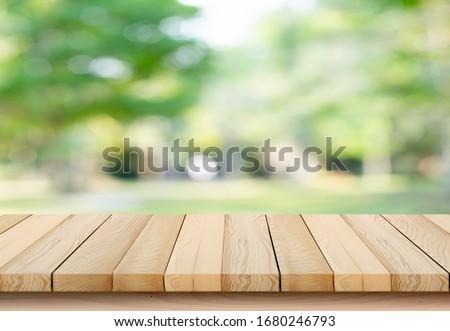 blurred background of green park in summer, Wood table top on shiny bokeh green background. For product display Royalty-Free Stock Photo #1680246793