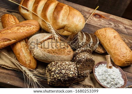 Fresh loaves of bread with wheat and gluten on a wooden table #1680253399