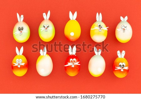 Colorful painted easter eggs with funny bunny ears and cartoon faces on red background