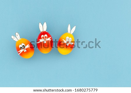Colorful painted easter eggs with funny bunny ears and cartoon faces on light blue background
