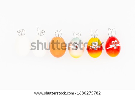 White, brown and colorful painted easter eggs with funny bunny ears and cartoon faces on white background