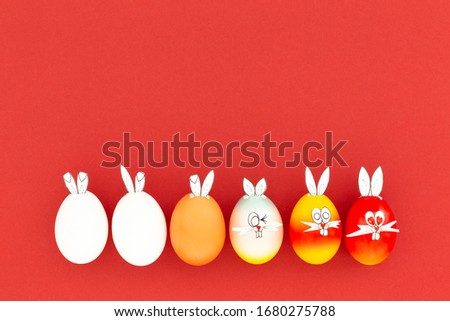White, brown and colorful painted easter eggs with funny bunny ears and cartoon faces on red background