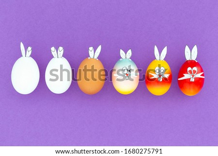 White, brown and colorful painted easter eggs with funny bunny ears and cartoon faces on purple background