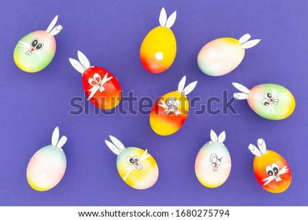 Colorful painted easter eggs with funny bunny ears and cartoon faces on purple background