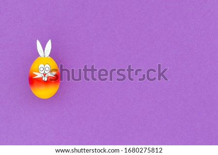 Colorful painted easter egg with funny bunny ears and cartoon face on purple background