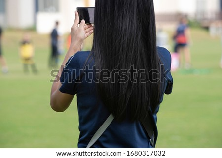 Mother standing, watching and taking pictures of her daughter playing football in a school tournament on a clear sky and sunny day. Sport, active lifestyle, happy family and soccer mom concept.
