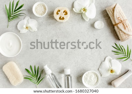 Spa treatment concept. Natural/Organic spa cosmetics products, sea salt, massage brush, tropic palm leaves on gray marble table from above. Spa background with a space for a text, flat lay, top view #1680327040