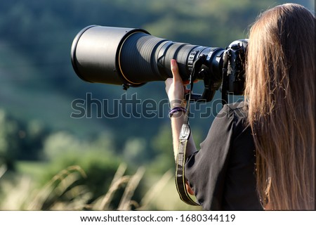 beautiful photographer with professional camera and very long optics