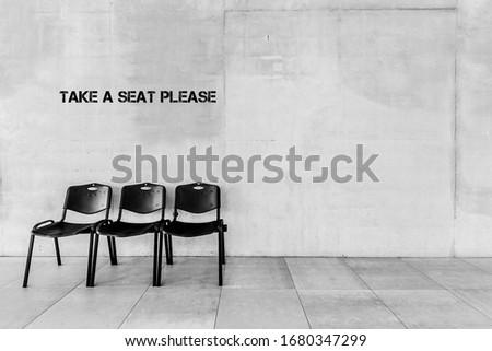 Photo of chairs in school with take a seat please writing on wall