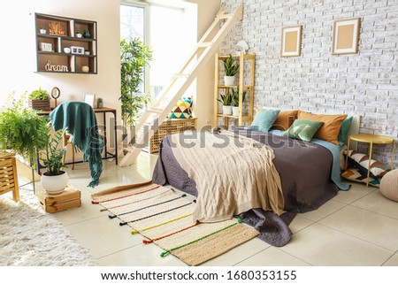 Interior of beautiful modern room with comfortable bed #1680353155
