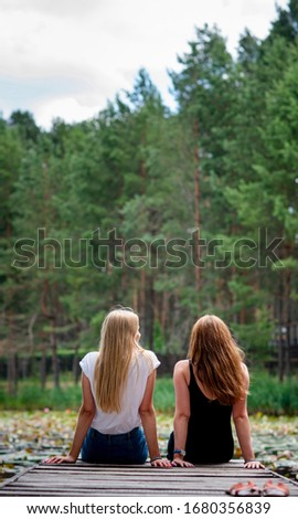 Two women are sitting together on pier enjoying the scenic view of a lake,back view.Female best friends enjoying a day.Beautiful romantic sunset image/girls on a river bank admires beautiful landscape